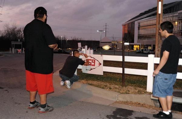 Mido Gutierrez (center) , Alex Calvillo (left) and Jorge Calvillo (right) place a sign outside the Kansas City Chiefs practice facility the evening that Chiefs player Jovan Belcher committed a murder and suicide.