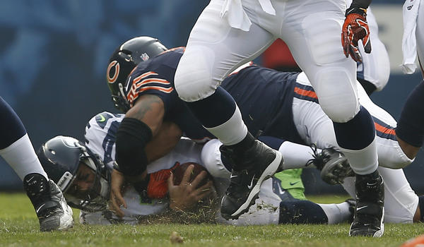 Defensive end Julius Peppers sacks Seahawks quarterback Russell Wilson in the first quarter.