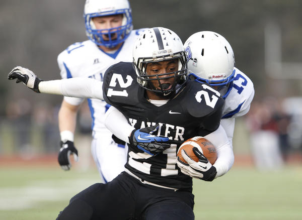 Xavier's DeAngelo Berry (21) is tackled by Glastonbury's Nick Karp (15) during the fourth quarter of the CIAC Class LL semifinal at Cheshire High School. The Falcons defeated the Tomahawks 30-13.