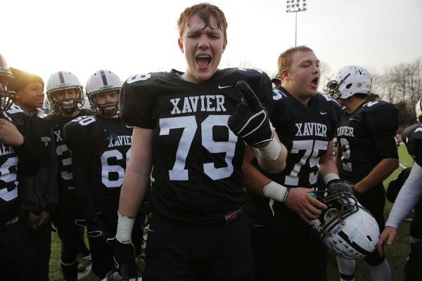 Xavier Falcons ol, dl Jonah Dorsey (79) and teammates celebrate their win over the Glastonbury Tomahawks in the CIAC Class LL semifinal at Cheshire High School. The Falcons defeated the Tomahawks 30-13.
