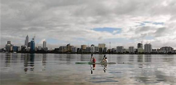 Kayakers paddle on the Swan River past the Perth city skyline