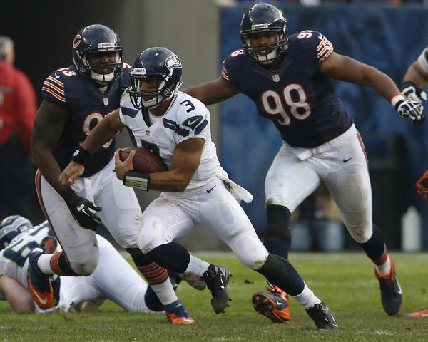 Seahawks quarterback Russell Wilson (3) runs for an 8-yard gain in the fourth quarter past Bears defensive end Corey Wootton (98) and defensive tackle Nate Collins (93).