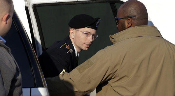 Army Pfc. Bradley Manning steps out of a security vehicle as he is escorted into a courthouse in Fort Meade, Md.