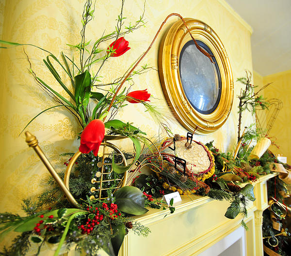 """Miller House Christmas theme features music decorations and antique music boxes and mantels decorated by area garden clubs. This mantel features a """"drum"""" made of moss, dried roses, and money plants."""