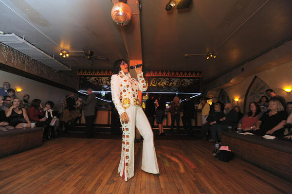 Debbie Knight of Lighthouse Point, Fla., performs as Elvis beneath a mirrored ball.