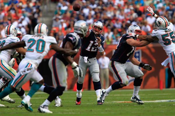 Quarterback Tom Brady #12 of the New England Patriots passes the ball to tight end Daniel Fells #86 of the New England Patriots during the game against the Miami Dolphins at Sun Life Stadium on December 2, 2012 in Miami Gardens, Florida. New England won 23–16.