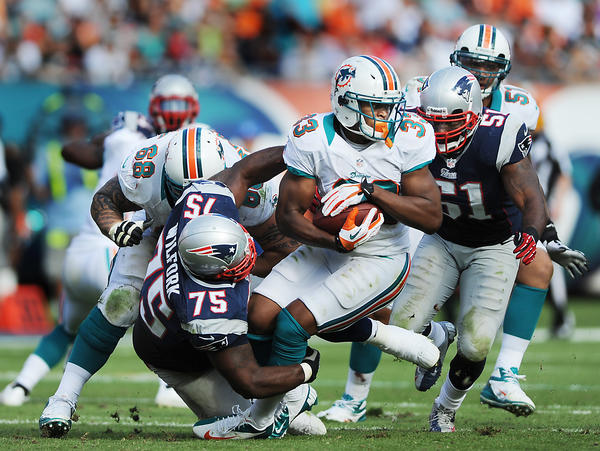 Miami's Daniel Thomas gets wrapped up by Vince Wilfork in the third quarter.