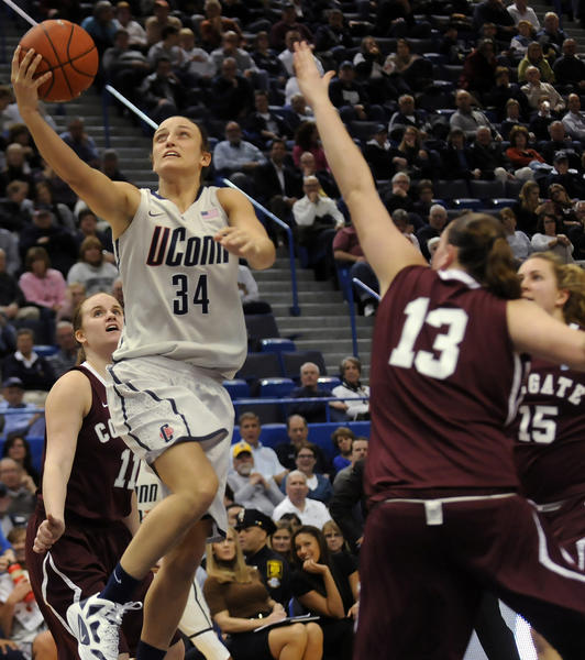 UConn guard Kelly Faris drives past the defense of Colgate guard Catherine Lewis (11) and center Lulu Brase (13) during the second half at the XL Center Wednesday night in Hartford. Faris scored 17 points and handed out five assists in a 101-41 victory.