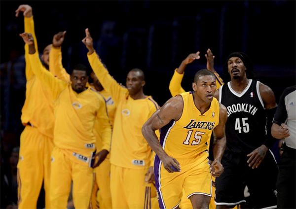 Lakers bench players celebrate a Metta World Peace three-pointer.