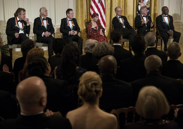Kennedy Center Honorees, from left: the surviving members of Led Zeppelin, Robert Plant, Jimmy Page and John Paul Jones, ballerina Natalia Makarova, talk show host David Letterman, actor Dustin Hoffman and blues musician Buddy Guy listen as President Obama speaks during the program in the East Room of the White House.