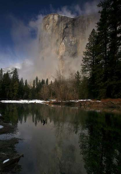 The iconic granite El Capitan is shrouded by fog on a winter day in Yosemite National Park.
