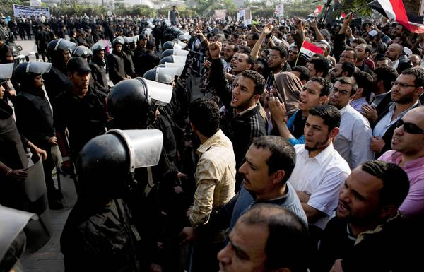 Supporters of Egyptian President Mohamed Morsi chant slogans as riot police stand guard at the entrance to Egypt's top court in Cairo.
