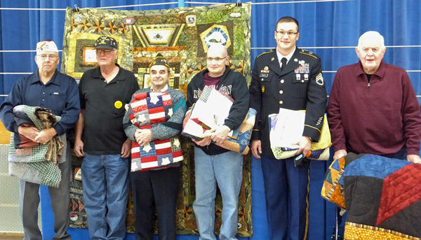 The South Dakota School for the Blind and Visually Impaired hosted a Veterans¿ Day program to honor those who have served in the armed forces. The program included a military color guard by the VFW Auxiliary Post No. 24, and the guest speaker was Chief Warrant Officer Merle Kjer. Quilts of Valor, under the direction of Jayne Reuer, were presented to seven veterans. The quilts are the school's way to say ¿thank you¿ for their service, sacrifice, and valor for the nation. Special music was provided by the students. From left are the quilt recipients: Ken Jorgenson (U.S. Army, Korean War); Kjer (U.S. Army, Vietnam War); Don Whittlinger (U.S. Navy, World War II); Terry Moffenbier (U.S. Air Force and U.S. Marines); Nick Abbas (S.D. Army National Guard, Operation Iraqi Freedom, Operation New Dawn); and Wayne Grunendike (U.S. Army, World War II, Battle of the Bulge). Honored, but unable to attend was Bernard Fischbach (U.S. Army, World War II).