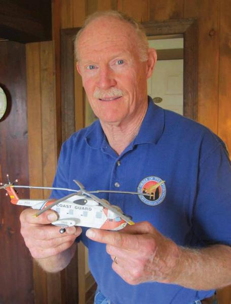 David Cooper, a recently retired helicopter pilot, shows a model of one type of helicopter he flew for search and rescue missions for the U.S. Coast Guard.