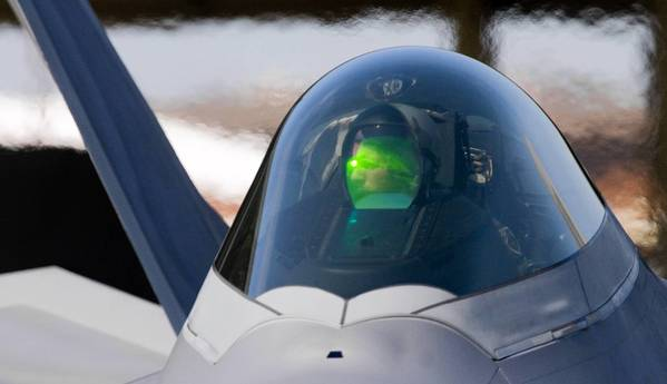 A heads-up display glows in the cockpit of an F-22 Raptor as the pilot taxis away from the aircraft shelter. It leaves a sea of heatwaves in its path as it to departs with other aircraft from 94th fighter squadron from Langley Air Force Base for an Air Expedionary Force deployment to Kadena Air Force Base, Japan.