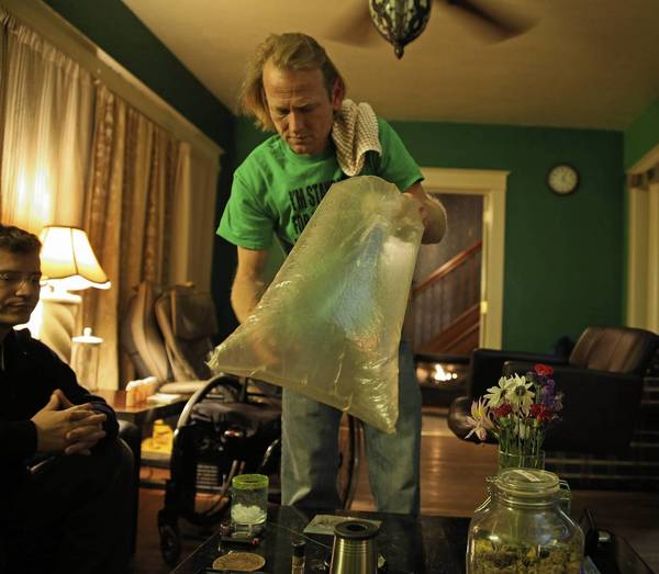 Karl Andrzejewski holds a plastic bag filled with marijuana vapor at his home in Kalamazoo, Mich., while his attorney John Targowski looks on. Andrzejewski, 42, was diagnosed with pancreatic cancer and is a registered medical marijuana patient and caregiver.