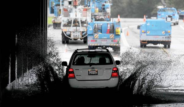 A car sends up plumes of water as it passes through a flooded underpass in San Rafael, Calif. as utility workers labor to repair a downed power line.