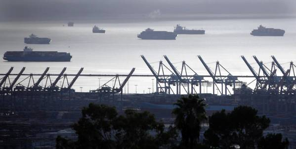About a dozen container ships sit offshore, unable to unload or load cargo. Ten more were due to arrive Monday. Above, ships sit offshore near idled cranes in the Port of Los Angeles.