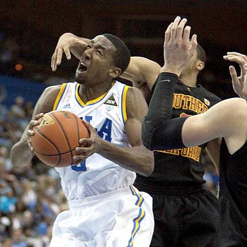 Bruins guard Malcolm Lee protects the ball, but not his head, from the swipe of Trojans guard Jio Fontan in the first half Wednesday night at Pauley Pavilion.