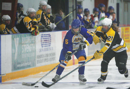 Hailey Gould of the Aberdeen Cougars (5) moves the puck up the ice as Heather Mullin (21) of the Watertown Lakers plays defense on Sunday at Odde Ice Center. American News Photo  by Ryan Deal