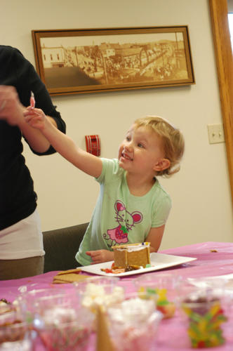 "Piper Stead, of Boyne City, smiles upon discovering a candy cane with which to decorate her gingerbread house, during a free activity at Boyne District Library Saturday. ""They do wonderful stuff like this at the library all the time,"" said her mother, Tina Stead."