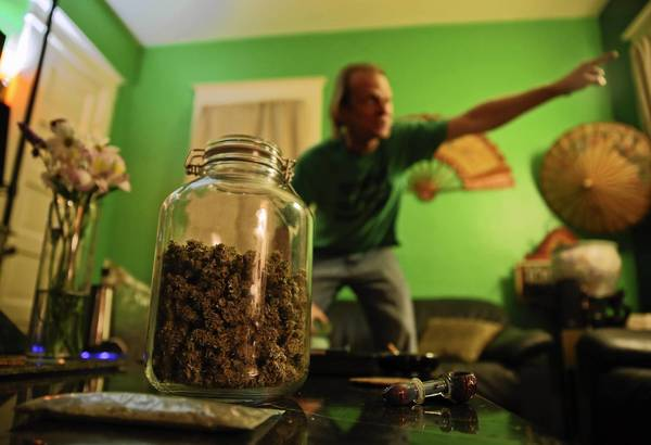 A jar containing about 2.5 oz of marijuana sits on a coffee table at the home of Karl Andrzejewski, background, in Kalamazoo, Mich. Andrzejewski is a legally licensed medical marijuana caregiver, which allows him to grow a specified amount of cannabis from his home and sell to patients.