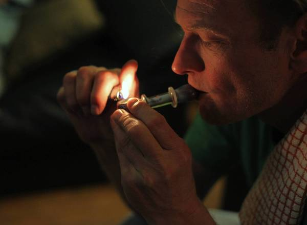 Karl Andrzejewski smokes marijuana from a pipe at his home in Kalamazoo, Mich. Andrzejewski is a legally licensed medical marijuana caregiver, which allows him to grow a specified amount of cannabis from his home and sell to patients. He was diagnosed with pancreatic cancer nine years ago, and after having his gall bladder removed, developed allergies to a variety of food proteins, in addition to chronic pain, which is part of the reason he grows cannabis for medical use.