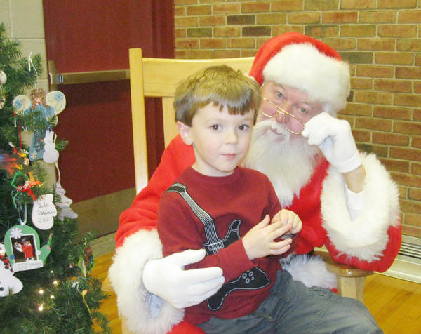 Finley Yurek, 5, enjoys sitting on Santa's lap and telling his Christmas wishes on Thursday during Petoskey Ottawa Elementary Parent Teacher Organization's family holiday craft night. In addition to crafts, cookies and hot chocolate were served, along with a visit from Santa.