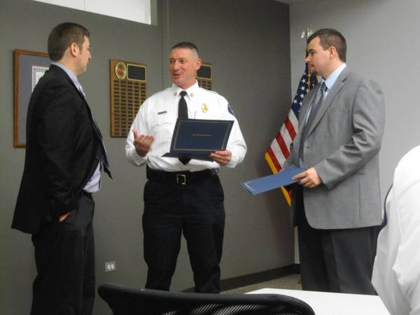 Brothers John Weimar, right, and Matthew Weimar, left, received an award from Fire Chief Ken Brucki during the Nov. 27 Orland Fire Protection District board meeting. The Orland Park brothers were credited with helping to save their father's life in September when he went into cardiac arrest in his home.