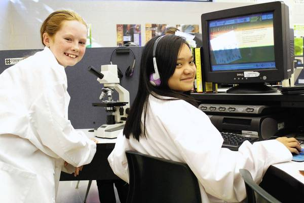 Seventh graders Grace O'Brien and Andrea Makilan work on a forensic science lesson in the applied technology lab at St. Alexander School in Palos Heights.
