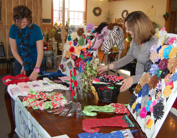 Lori Carmicle, left, and Malory Coffman, the two friends behind Doodads, arrange their table at Saturday's event in Liberty.