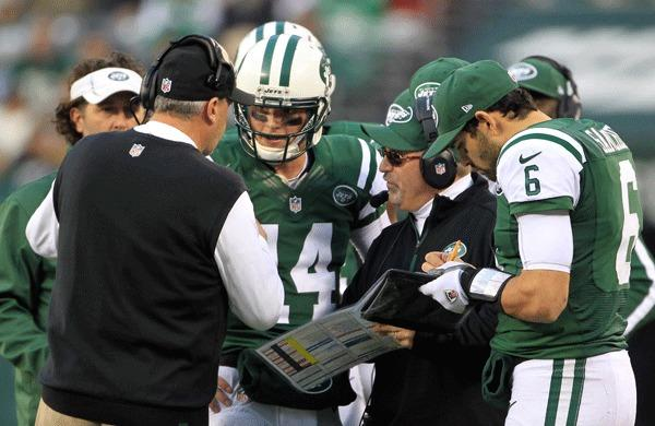New York Jets head coach Rex Ryan (left) talks with quarterback Greg McElroy (14) and quarterback Mark Sanchez (6) during the game against the Arizona Cardinals at Metlife Stadium.