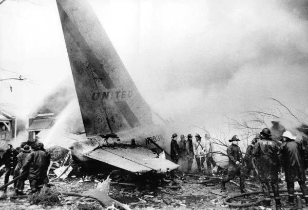 Firefighters work at the scene where United Airlines Flight 533 crashed into a row of bungalows on West 70th Place while approaching Midway Airport.