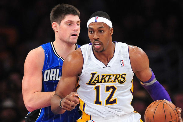 Los Angeles Lakers center Dwight Howard (12) controls the ball against the defense of Orlando Magic center Nikola Vucevic (9) during the first half at Staples Center.