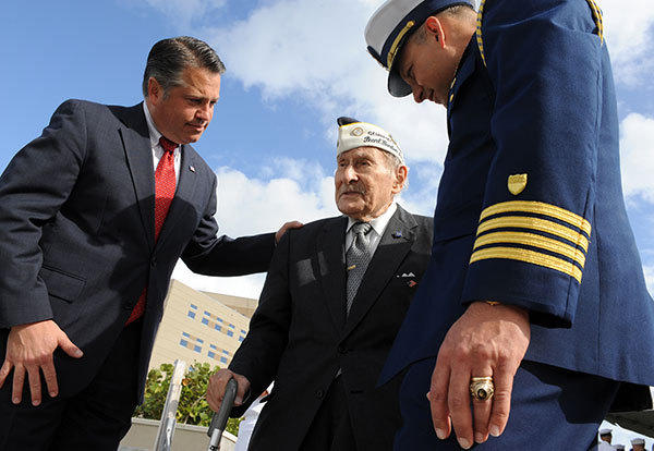 Army Staff Sergeant Abe Stein, 92, of Aventura (center), Captain Richard M. Kenin, Chief of Staff, Seventh Coast Guard District (right), along with Broward commissioner Chip LaMarca (left) prepare to toss a wreath into the waters of Port Everglades for a ceremony commorating the attack on Pearl Harbor, Hawaii on December 7, 1941. The ceremony was held at the Fort Lauderdale Coast Guard station, located at the northern tip of John U. Lloyd State Park.
