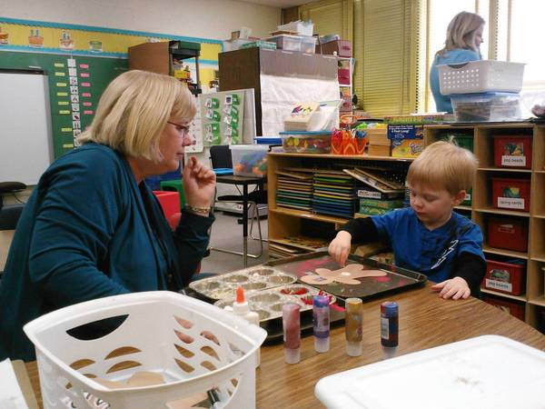Aide Vicki Winter helps Aeden, 3, decorate a gingerbread man during a play period at Jefferson Early Childhood Center this month.