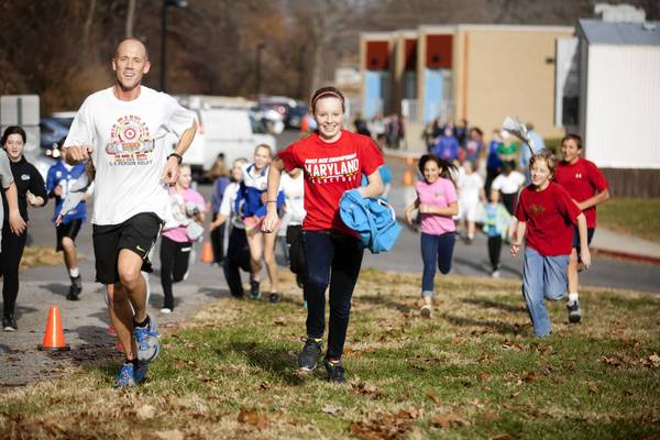 Hammond Middle School eighth-grader Kate Lastova, right, keeps stride with math teacher Matt LaCorte during the school's Accelerate Ethiopia Fun Run on Nov. 30.