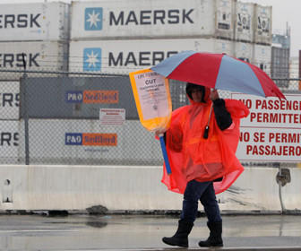 A striking worker walks the picket line outside the Port of Los Angeles on Friday.