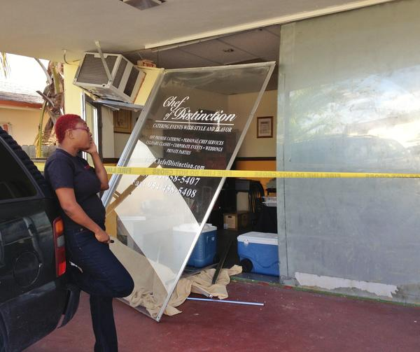 Chef Judith Able waits for workers to repair the front entrance to her Hallandale Beach catering shop. A butane torch exploded inside the shop on Monday.
