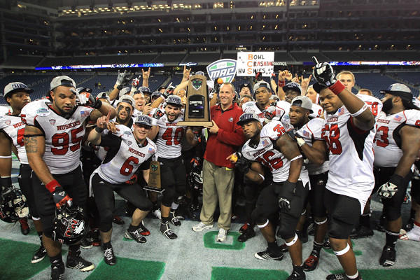 DETROIT, MI - NOVEMBER 30: Head coach Dave Doeren of the Northern Illinois Huskies is surrounded by his team as he holds the championship trophy after defeating the Kent State Golden Flashes 44-37 during the Mid-American Conference Championship game at Ford Field on November 30, 2012. (Photo by Dave Reginek/Getty Images)