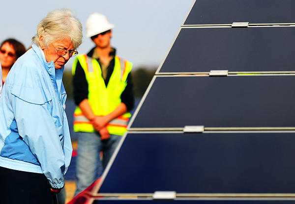 Hagerstown Community College student Jone Thurmond studies a solar array Monday at the solar farm on Roxbury Road. Andy Hershberger, installation project manager for Belectric Inc., looks on.