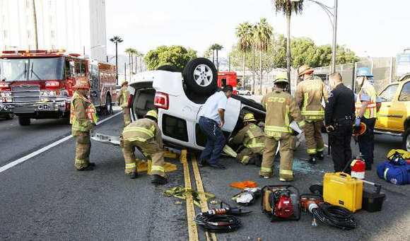 Firefighters work to remove the driver of an SUV, suspended by her safety belt, at the scene of a roll-over crash on Brand Blvd. near Chevy Chase, involving three vehicles on Monday, December 3, 2012.