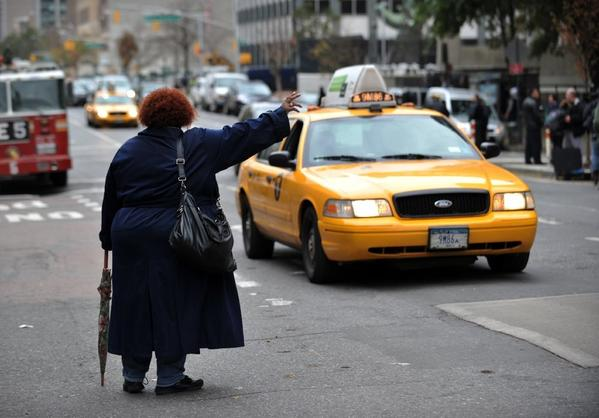 A woman tries to hail a taxi on First Avenue in New York.