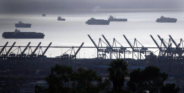Container ships lie off shore near idled cranes in the port of Los Angeles in San Pedro. Striking clerical workers have slowed down or stopped operations in the Ports of Los Angeles and Long Beach
