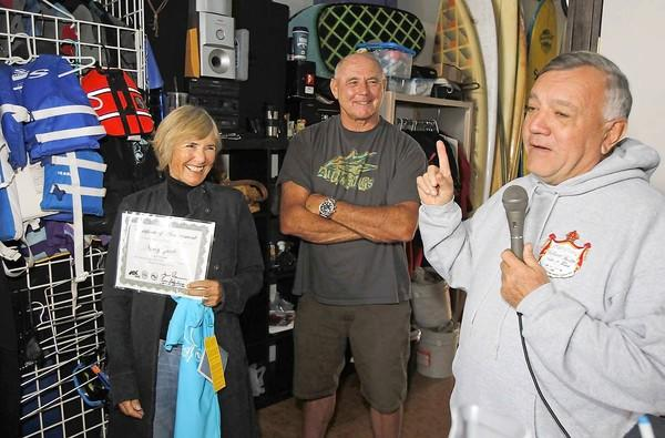 Bruce Gabrielson, right, of the National Surf Schools and Instructors Assn., says a few words as Newport Beach Mayor Nancy Gardner, left, is presented with an honorary certificate as possibly the first and only stand-up paddleboarding mayor. Former pro surfing champion and stand-up paddleboarding coach and advocate Ian Cairns stands in the middle.