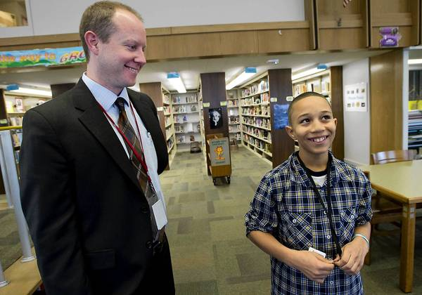 Erich May, (left) an instructional supervisor at Trexler Middle School in Allentown, speaks with sixth grader Job Rodriguez, 10, a native of the Dominican Republic. May is going to the Dominican Republic on Tuesday to help build a school.