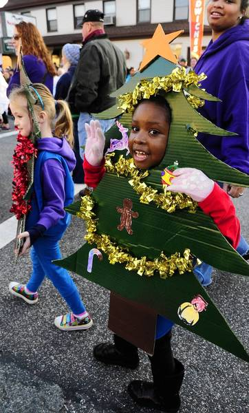 Pharren Vinson spreads some holiday joy to the crowd as she and fellow Girl Scouts from Service Unit 76 of Aberdeen march along West Bel Air Avenue in Aberdeen's Christmas Street Parade Saturday.