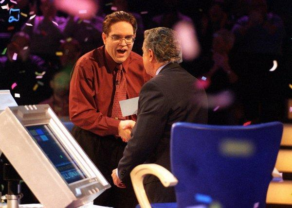 "Host Regis Philbin congratules winning contestant Kevin Olmstead on ""Who Wants to be a Millionaire?"" in 2001"