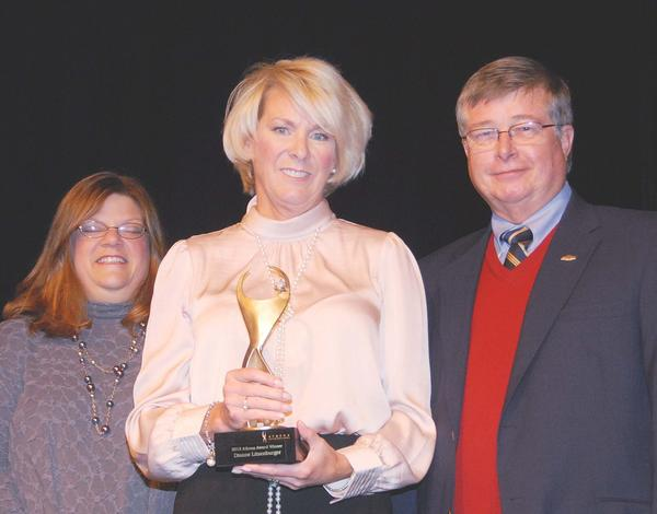 Dianne Litzenburger (center), director of communication services with Charlevoix-Emmet Intermediate School District, displays the Athena Award she received for 2012 at Petoskey's Breakfast for Champions. Presenting the award to Litzenburger were the 2011 Athena winner, the Rev. Sherry McGuffin (left) and award sponsor and local auto dealership owner Dave Kring.