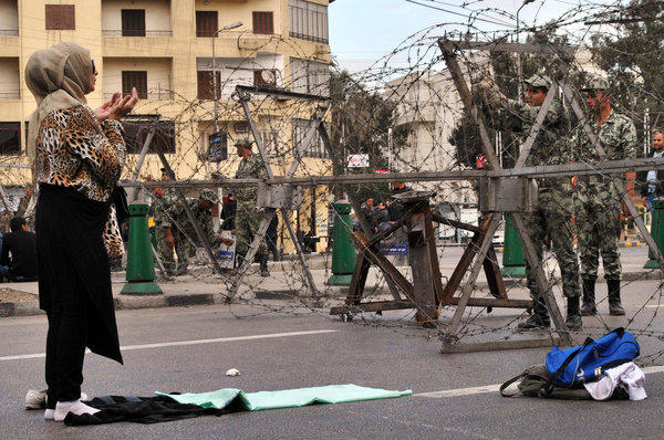 A Egyptian woman prays in front of security forces as they lay out barbed wire along streets leading to the Itihadiya presidential palace in the Heliopolis neighborhood of Cairo ahead of protests on Tuesday.